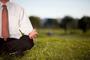 Businessman meditating in a park